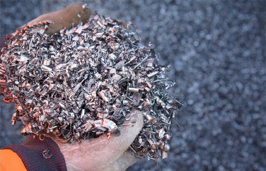Gloved hand holding scrap tin shavings